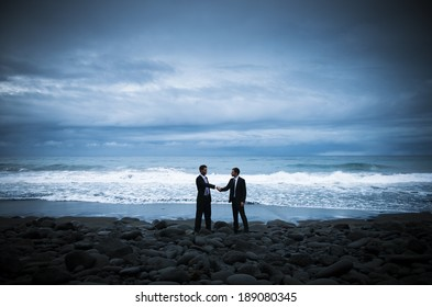 Two Businessmen Shaking Hands At Stormy Beach
