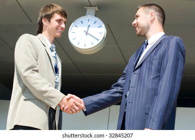 Two businessmen shaking hands under large clock