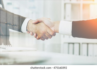 Two businessmen shaking hands in white office with bookshelves and table. Concept of good business deal