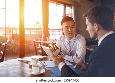 Two businessmen sitting in cafe and discussing business project