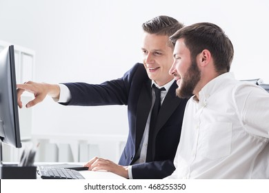 Two businessmen sitting at computer table. One is pointing at screen. They work together and smile. Concept of collaboration