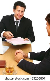 Two businessmen sitting at a table negotiating and signing a contract.