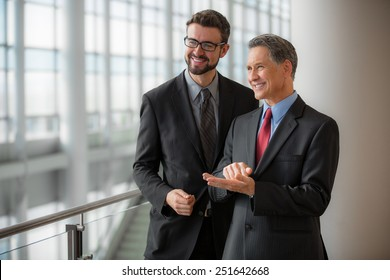 Two businessmen smiling at the office