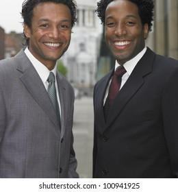 Two businessmen smiling outdoors