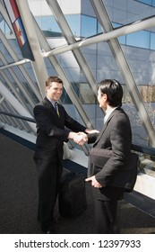 Two businessmen smiling and shaking hands in an office lobby