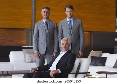 Two businessmen standing behind their sitting leader : top 3 portrait.
