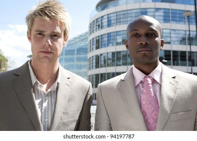 9d81b0cb68a Two businessmen standing by a modern office building.