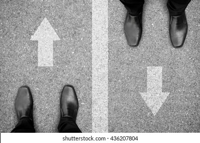 Two businessmen standing on different side of the road. Representing rivals, enemies, competitors in business and life.