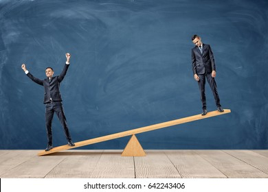Two businessmen standing on a wooden seesaw, one happy and one sad looking. Success and failure. Business and workplace competition. Losers and winners.