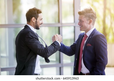 two businessmen standing outside, smiling and shaking hands