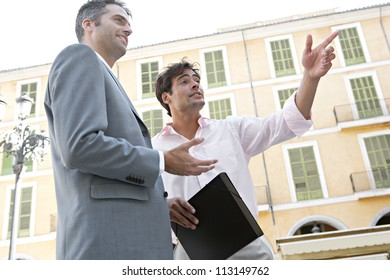 Two businessmen standing and talking near a classic building in a European city.