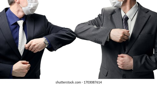 Two businessmen in suits greet each other without a handshake due to the danger of infection