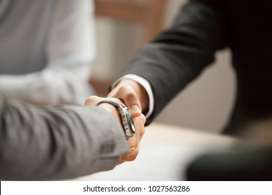 Two businessmen in suits shaking hands at group meeting, partners handshaking at negotiations making deal or signing contract, thanking for help support, welcome greeting handshake concept, close up