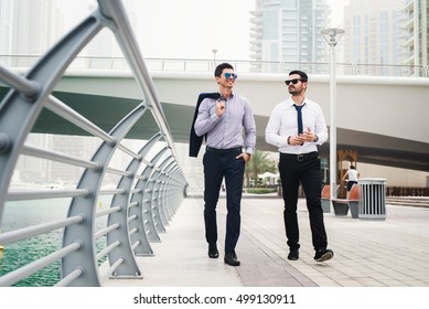Two businessmen talking during the walk through Dubai Marina.