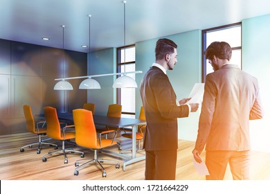 Two businessmen talking in stylish meeting room with blue walls, wooden floor and long conference table with orange armchairs. Windows with blurry cityscape. Toned image