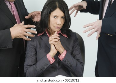 Two businessmen threatening a businesswoman with harassment.