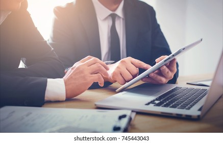 Two businessmen using touchpad at meeting