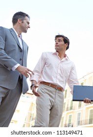 Two businessmen walking passed a building in a European city while having a conversation.