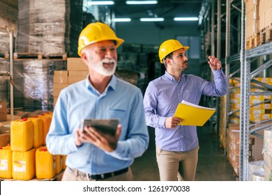 Two businessmen in warehouse. Selective focus on younger one with helmet on head and folder with documents in hand.