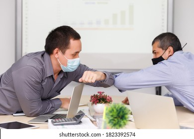 Two businessmen wear protective face mask new novel greeting with elbow bump instead of a handshake before the meeting as social distance practice prevent coronavirus COVID-19.