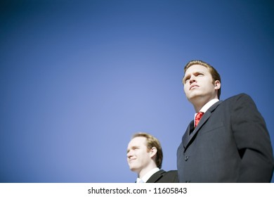 Two businessmen wearing suits posing with determined vision pose