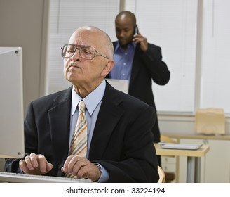 Two businessmen are working in an office.  The older man is working on a computer and the younger man is talking on a cell phone.  Horizontally framed shot.