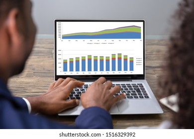 Two Businesspeople Analyzing Financial Graph On Laptop