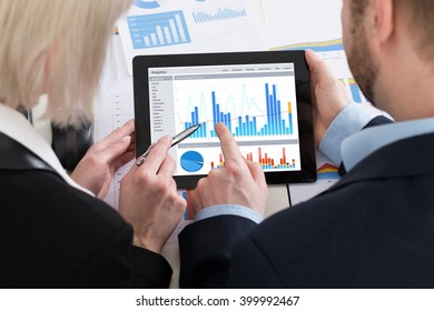 Two Businesspeople Analyzing Graph On Digital Tablet In Office
