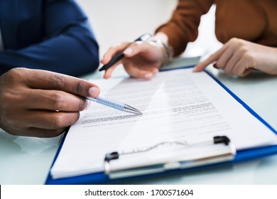 Two Businesspeople Hand Analyzing Document Over Glass Desk