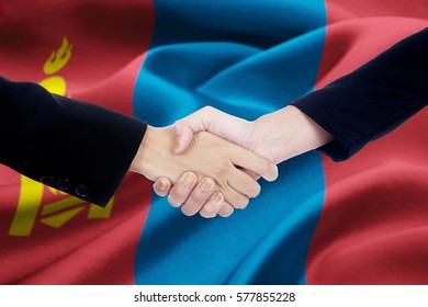 Two businesspeople hands in a business suit, shaking hands with Mongolian flag background