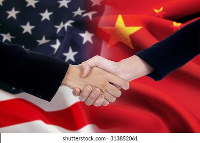 Two businesspeople handshake after good deal in front of an american and chinese flag