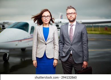 Two businesspeople looking at camera on windy day