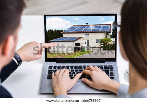 Two Businesspeople Looking At House On Computer Screen