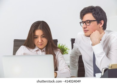 Two businesspeople looking at laptop screen in office