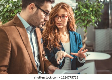 Two businesspeople in a serious discussion are standing in the office together looking at business plan.
