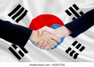 Two businesspeople shaking hands in front of south korean flag background