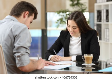 Two businesspeople signing contracts together after a deal in a desktop at office