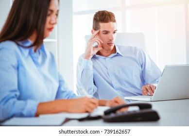 Two businesspeople sitting at the office table. Woman is writing and man looking at laptop. Selective focus. Focus on background, on man.