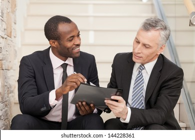 Two businesspeople sitting on stairs and looking at papers.