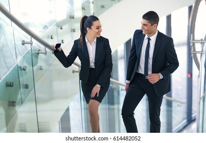 Two businesspeople talking as they walk into the office