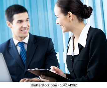 Two businesspeople working with document at office. Focus on woman.