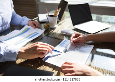 Two Businesspeople Working On Gantt Chart Over Wooden Desk In Office
