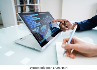 Two Businesspeople Working Together With Financial Graph On Laptop