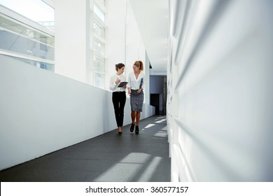 Two businesswoman dressed in formal wear laughing at funny video on digital tablet during work break, young attractive female holding touch pad and talking about something cheerful to her partner