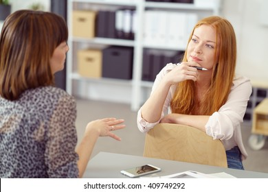 Two businesswoman having an informal meeting with one sitting relaxing on a reversed chair listening to her colleague with a pensive expression - Shutterstock ID 409749292