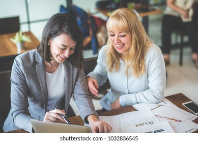 Two businesswoman working together with laptop and paperwork at coffee shop, color tone effect