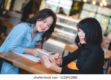 Two businesswoman working together with tablet and paperwork at coffee shop in the morning