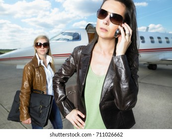 Two businesswomen beside private jet.