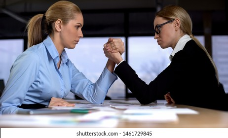 Two businesswomen doing arm wrestling in office, concept of rivalry at work