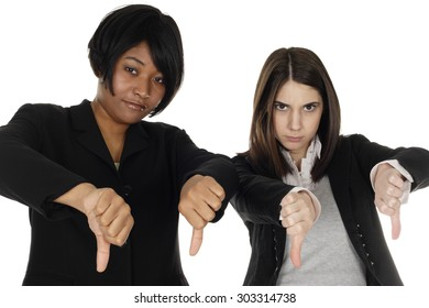 Two businesswomen give thumbs down.